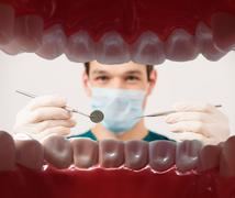 View at young male dentist holding dental tools from patient mouth Stock Photos