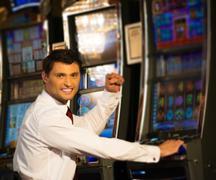 Handsome happy brunette man in white shirt near slot machine Stock Photos
