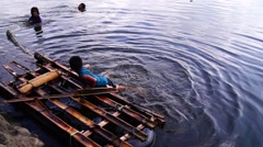 Children swim in lake water with bamboo raft Stock Footage