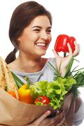 smiling  brunette woman with grocery bag full of fresh vegetables and red pap - stock photo