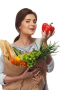 Smiling  brunette woman with grocery bag full of fresh vegetables and red pap Stock Photos
