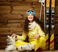 Happy woman with skis and ski boots sitting on a floor near wooden wall Stock Photos