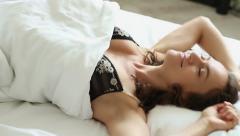 Woman falling backward onto bed, slow motion  HD Stock Footage