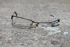 Broken eyeglasses on concrete Stock Photos