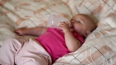 little baby lying on the bed and drinking milk from a bottle - stock footage