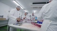 Group of butchers working in a fresh meat processing factory - stock footage