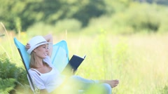 Young woman reading book in outdoor chair Stock Footage