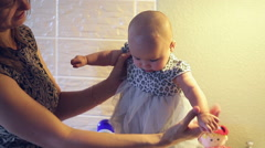 Mom keeps a little baby girl in a dress in her hands Stock Footage