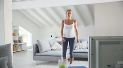 Young woman doing fitness exercises in front of tv Stock Footage