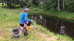 Girl fishing at pond and play with little cat. Free time nature Stock Footage
