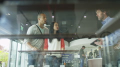 Helpful salesman serving customers in consumer electronics store showroom - stock footage