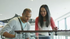 Couple shopping in consumer electronics store showroom - stock footage