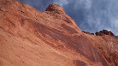 Pan red rock cliff in southern Utah, blue sky & white cloud - stock footage