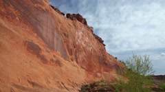 Pan tilt red rock cliff to tree in southern Utah, blue sky & white cloud - stock footage
