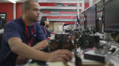 Workers in an electronics factory working on computer testing and repairs - stock footage