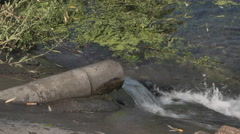 Taksicheskih release waste into the lake from the pipe Stock Footage