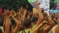 Crowd covered in colorful paint jumping to music at festival Stock Footage