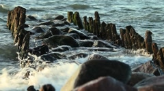 Waves wash over groynes wellen brechen sich an buhne Stock Footage