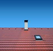 Roof with brown tiles on a background of blue sky, new roof Stock Photos