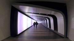 Passengers for London's Kings Cross Station walk down the new light wall walkway Stock Footage