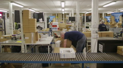 Workers in electronics factory warehouse packaging goods & preparing deliveries - stock footage