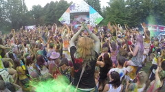 People spraying colored powder paint at festival, slow motion, click for HD Stock Footage