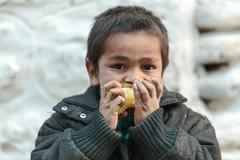 Nepalese kid eating an apple Stock Photos