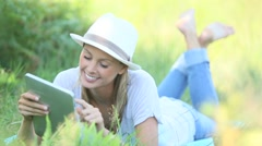 Relaxed woman using digital tablet in country field Stock Footage