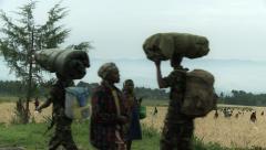 Harvesting in Rwanda while local people cross the shot Stock Footage