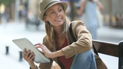 Trendy girl using tablet sitting on bench in town Stock Footage
