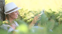 Woman in park enjoying novel Stock Footage