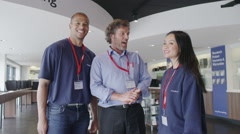 Helpful team of staff ready to serve customers in consumer electronics store - stock footage
