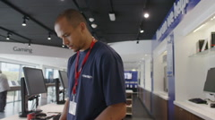 Helpful team of staff working on computers in consumer electronics store - stock footage