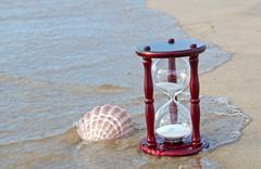 sand timer with seashell - stock photo