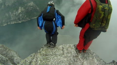 Base jumper jumping of a cliff for an extreme sport - stock footage