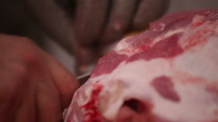 Butcher trimming pork ham Stock Footage