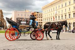 Coachman sits on a carriage, pulled by a horse, waiting for tourists to piazz Stock Photos