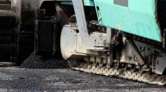 Machine for paving apply asphalt to road. Worker with shovel taking asphalt. - stock footage