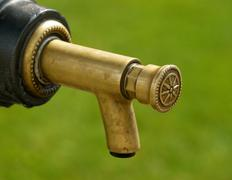 detail of tap on metal drinking fountain - stock photo