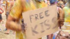 Guy covered in paint holding free kiss sign, music festival, click for HD Stock Footage
