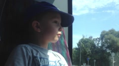 Small child (boy) travel by bus and looks out the window at the urban street Stock Footage