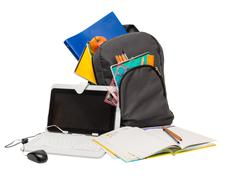 school backpack with school supplies and a tablet computer . - stock photo