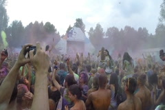 Colorful powder paint above people's heads at concert, slow-mo, click for HD Stock Footage