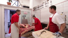 Butchers hanging beef pork carcasses on hooks Stock Footage