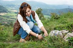 young woman admires the flowers at the mountain meadow - stock photo