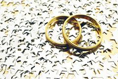 Gold wedding rings with silver stars on gold background Stock Photos