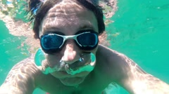 Slow motion of a man breathing out air bubbles underwater Stock Footage