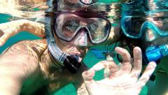 Underwater snorkeling couple doing ok sign - slow motion - stock footage