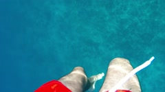 Underwater swimming in the sea in red swimwear - slow motion Stock Footage