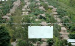 Sign board fastened to a barbed wire fence Stock Photos